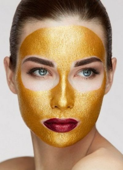 Cosmetology Mask. Young Woman With Gold Face Mask On Soft Skin